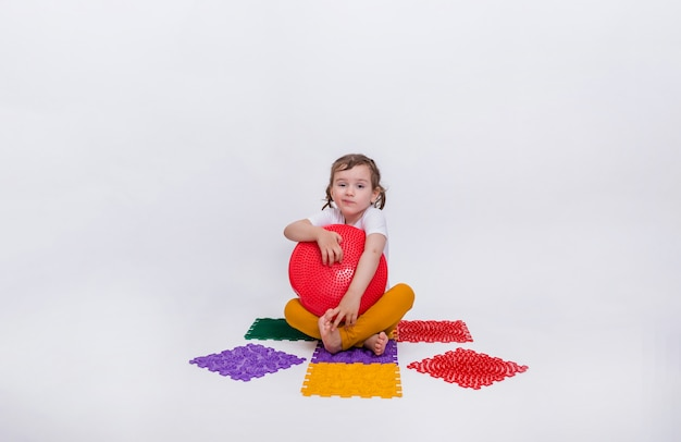Una bambina carina è seduta su un colorato tappetino ortopedico con un cuscino rosso equilibrante. prevenzione dei piedi piatti