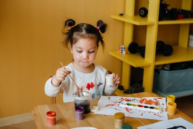 Una bambina carina gioca e dipinge nella sua stanza. ricreazione e intrattenimento.