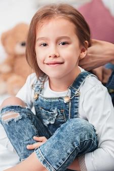 Una bambina carina godendo, giocando e creando con le mani della madre