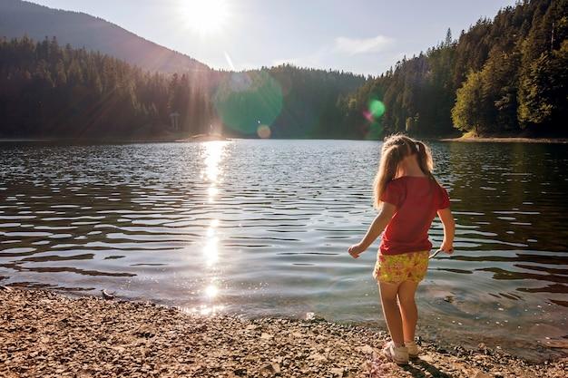 Una bambina carina plaing sulla riva di un lago di montagna