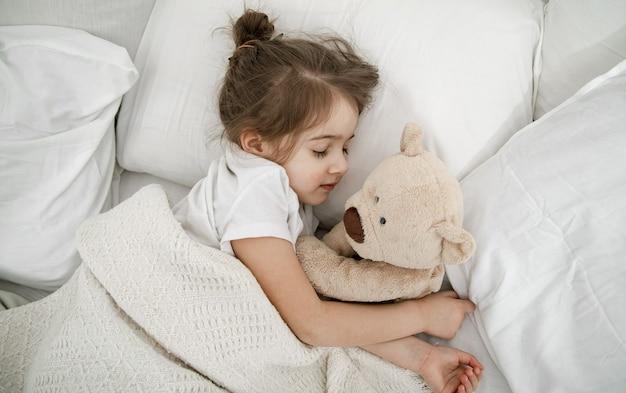 Una bambina carina sta dormendo in un letto con un orsacchiotto. concetto di sviluppo del bambino e sonno. la vista dall'alto.