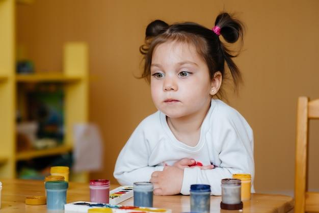 Una bambina carina sta giocando e dipingendo nella sua stanza. divertimento e intrattenimento.