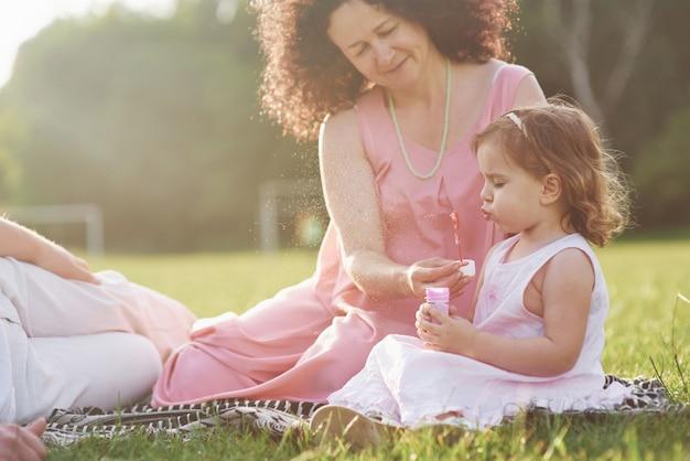 Una bambina carina sta trascorrendo del tempo con il suo amato nonno e nonno nel parco. hanno fatto un picnic sull'erba