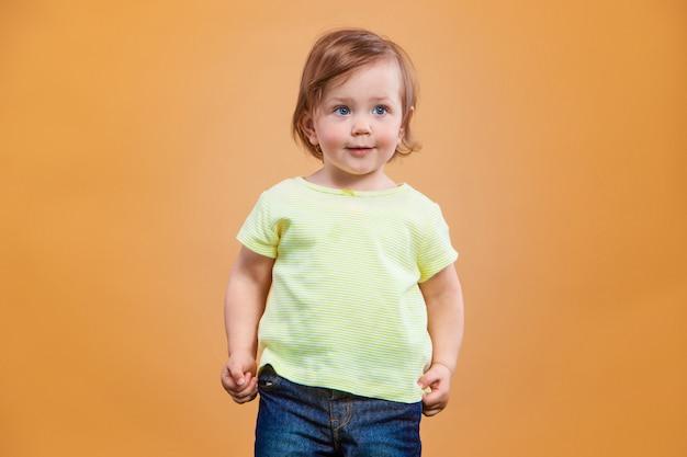 Una bambina carina su spazio arancione
