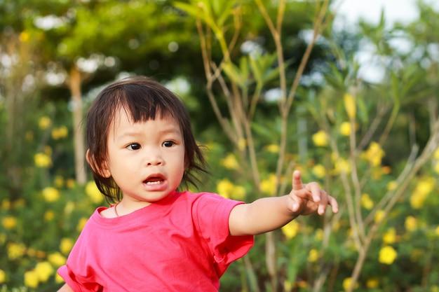 Una bambina che punta il dito a sinistra in giardino.