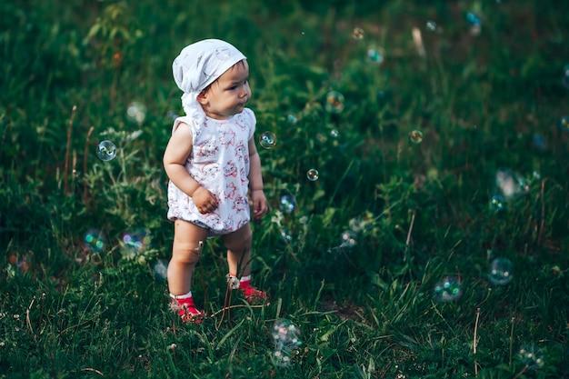 Una bambina che soffia bolle di sapone, ritratto di primavera bellissimo bambino di un anno