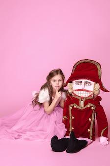 Una bambina come ballerina di bellezza in abito lungo rosa con schiaccianoci in studio rosa