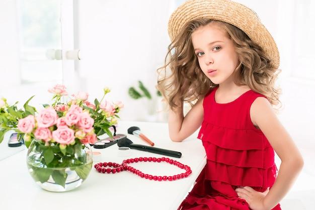 Una bambina con abito rosso e cosmetici.