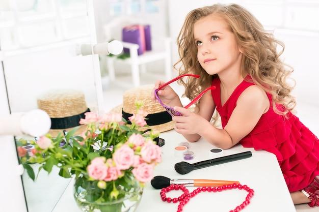 Una bambina con cosmetici. è nella camera da letto della mamma, seduta vicino allo specchio.
