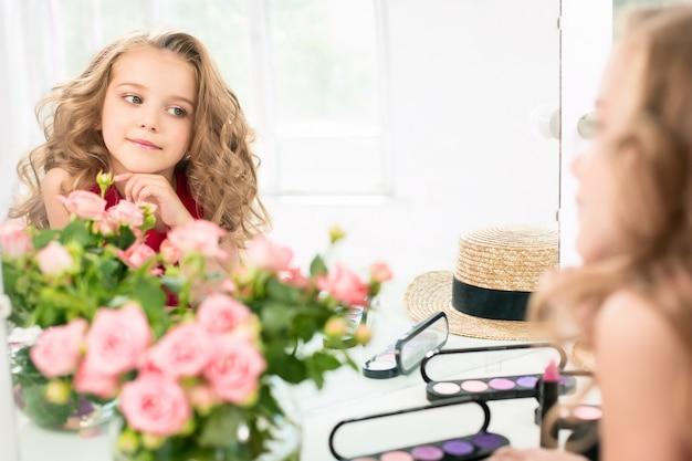 Una bambina con cosmetici seduti vicino allo specchio.