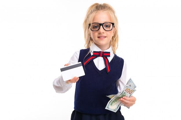 Una bambina con i capelli biondi infilati in una coda di cavallo, grandi occhi blu e una faccia carina in occhiali neri quadrati con un pass e dollari.
