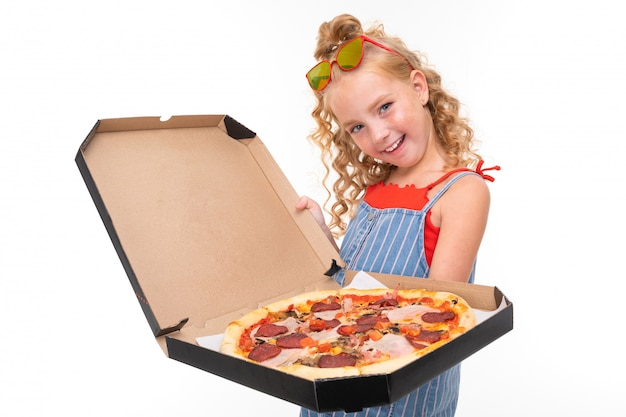 Una bambina con i capelli heap rossi in una maglia rossa e tuta blu e bianca in una striscia tiene una grande pizza in una scatola.