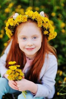Una bambina con i capelli rossi sorride contro un campo di denti di leone e di erba verde.