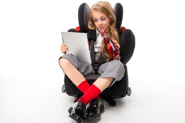 Una bambina con il trucco e lunghi capelli biondi seduto in una sedia per bambini auto con tablet, bere succo e guardare interessante film di cartone animato