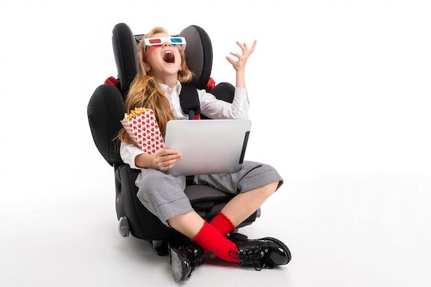 Una bambina con il trucco e lunghi capelli biondi seduto su una sedia per bambino con tablet, auricolari, pop-corn, occhiali 3d e guardare un film commedia interessante di cartoni animati