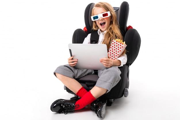 Una bambina con il trucco e lunghi capelli biondi seduto su una sedia per bambino con tablet, auricolari, pop-corn, occhiali 3d e guardare un interessante film di cartone animato