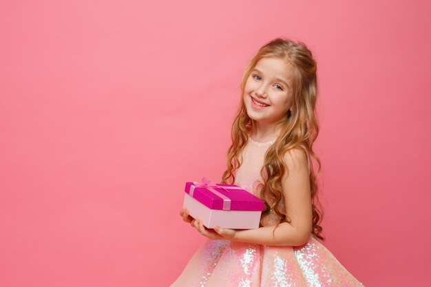 Una bambina con in mano un regalo sorride su uno spazio rosa.