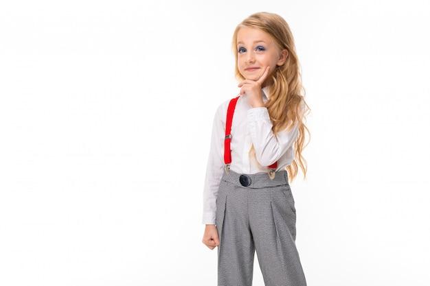 Una bambina con lunghi capelli biondi in una camicia bianca, pull-up rossi, pantaloni in una gabbia, calze rosse e scarpe con brillanti sogni di trucco.