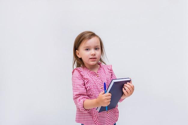 Una bambina con un blocco note e una penna in una camicia controllata su un bianco isolato