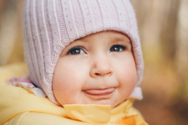 Una bambina con un cappello caldo in testa sorrise. infanzia, salute, fecondazione in vitro, tempo freddo
