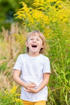 Una bambina con una maglietta bianca sta tra i fiori gialli autunnali nel campo e sorride.