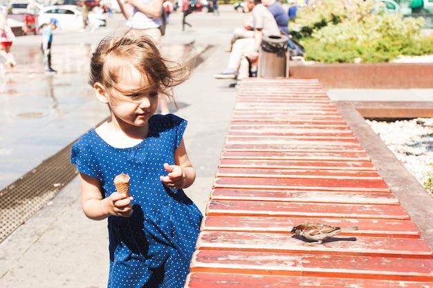 Una bambina dà da mangiare pane all'uccello, passero, animali e bambini, gelati, città ed estate