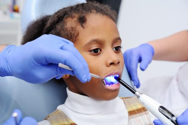 Una bambina dalla pelle scura sulla sedia del dentista
