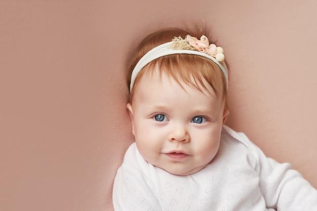 Una bambina di quattro mesi giace su un muro rosa chiaro