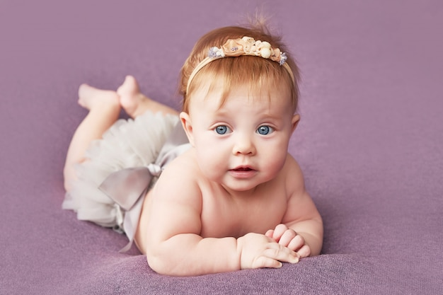 Una bambina di quattro mesi si trova su un muro viola