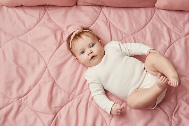 Una bambina di quattro mesi si trova su una parete rosa