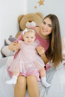 Una bambina di un anno è una bambina tra le braccia di sua madre. mamma e figlia sorridenti felici