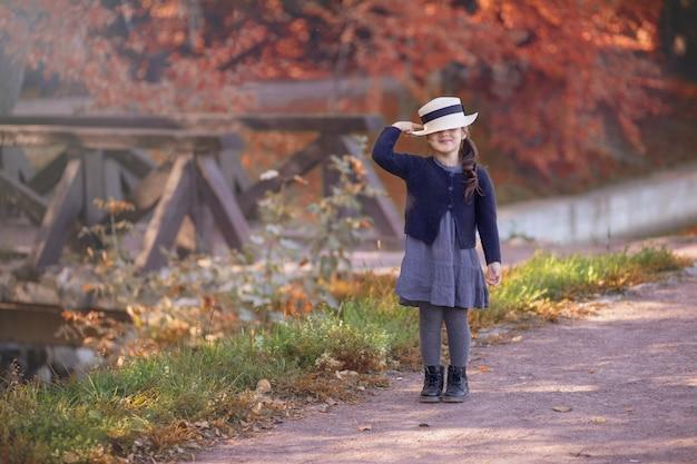Una bambina divertente sta sorridendo in abiti vintage, chiuse gli occhi con un cappello di paglia