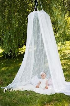 Una bambina è seduta sotto un baldacchino su una coperta bianca in un parco. una ragazza carina distoglie lo sguardo in un abito bianco e fascia in natura.
