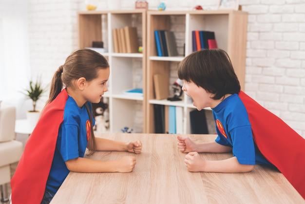 Una bambina e un ragazzino in completo di supereroi.