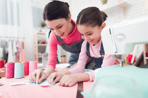 Una bambina e una donna costruiscono insieme i vestiti.