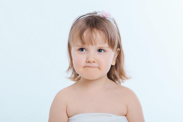 Una bambina fa smorfie contro uno sfondo bianco. il bambino sta facendo qualcosa. concetto di emozioni, espressioni facciali, infanzia, sincerità