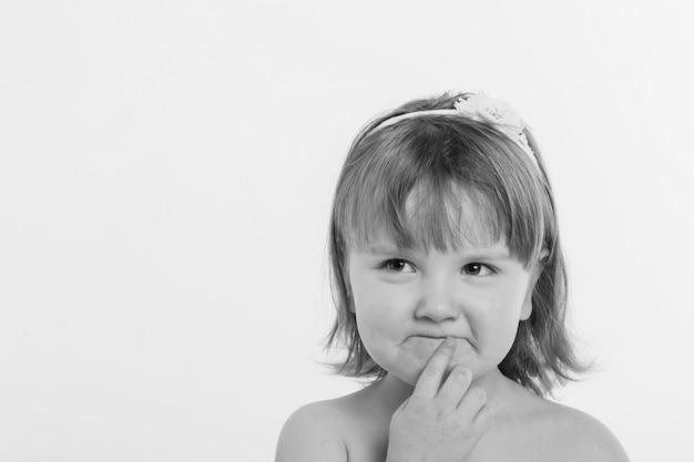 Una bambina fa smorfie contro uno sfondo bianco.