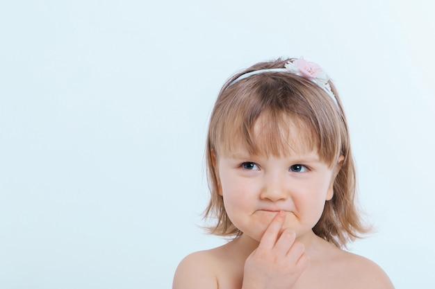 Una bambina fa una smorfia. il bambino sta facendo qualcosa. concetto di emozioni, espressioni facciali, infanzia, sincerità