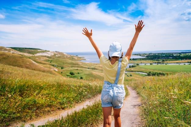 Una bambina felice in una tuta di jeans corre con le mani aperte contro un paesaggio pittoresco
