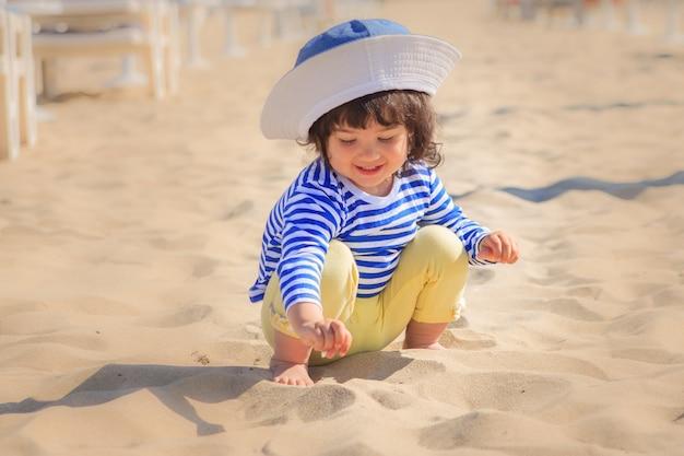 Una bambina gioca a sabbia sulla spiaggia