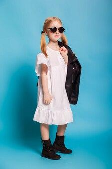 Una bambina in abito bianco e scarpe nere
