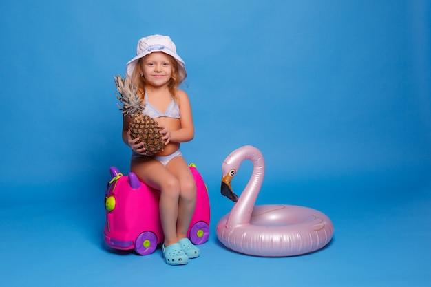 Una bambina in costume da bagno con un ananas in mano si siede su una valigia su sfondo blu. concetto di viaggio