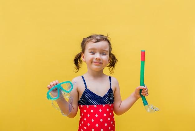 Una bambina in costume da bagno con una maschera e un tubo su un giallo isolato
