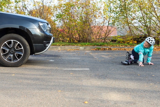 Una bambina in giacca blu e casco sui rulli cadde di fronte a un'auto in movimento su una strada cittadina