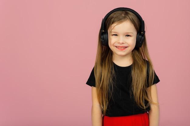 Una bambina in grande cuffia nera senza fili. il concetto di ascoltare e ascoltare musica. posto per testo, copyspace