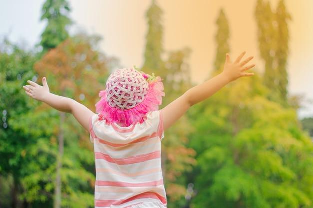 Una bambina in piedi sull'erba, alzando due mani su uno sfondo naturale.