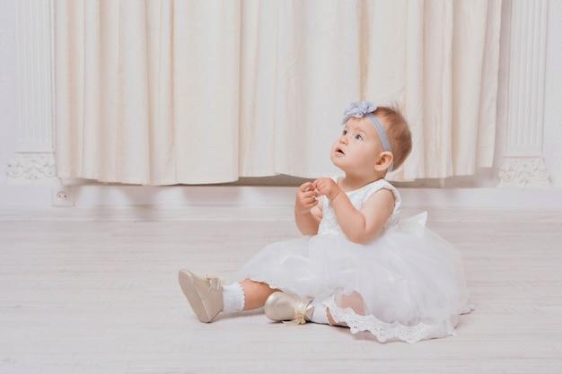 Una bambina in un abito si siede sul pavimento su uno sfondo bianco. il bambino promuove i vestiti dei bambini
