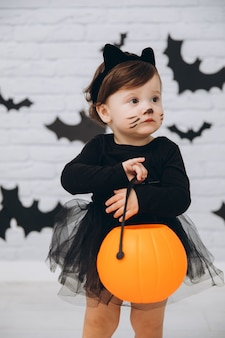 Una bambina in un costume da gatto nero con un cesto di zucca