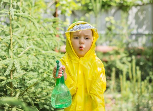 Una bambina in un impermeabile giallo con una pistola a spruzzo in una serra di conifere guarda la telecamera con un'espressione perplessa