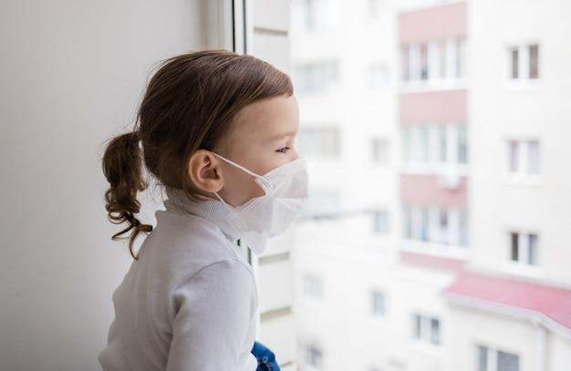 Una bambina in una maschera si siede sul davanzale di una finestra e guarda fuori dalla finestra